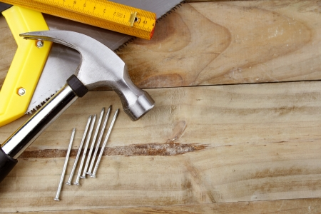 carpentry tools: Hammer, nails, saw and folding ruler on wood