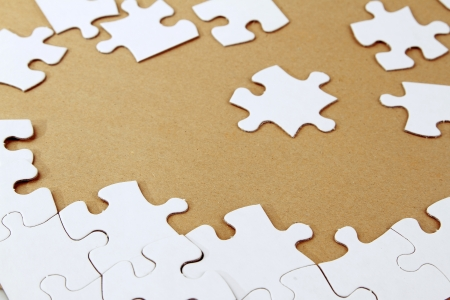 scattered: Loose jigsaw puzzle pieces on brown background Stock Photo