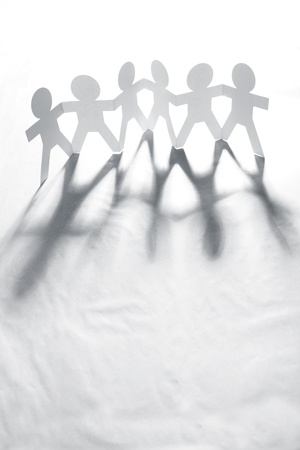Group of six paper chain people holding hands together photo