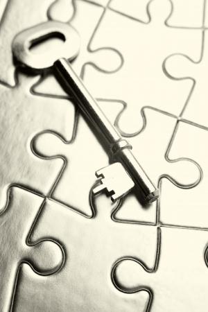 Single key resting on jigsaw puzzle Stock Photo - 17381125