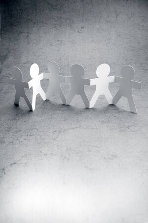 Group of paper chain people holding hands together. Stock Photo - 17455317