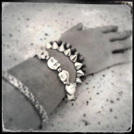 vodoo: Bracelets on arm, focus on skulls