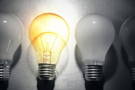 odd one out: One bright bulb in line of dull light bulbs  Standing out concept