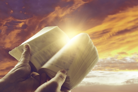 bible reading: Hands holding open book in front of sky