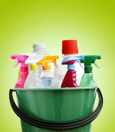 schoonmaakartikelen: Het reinigen van flessen in emmer. Groene achtergrond Stockfoto