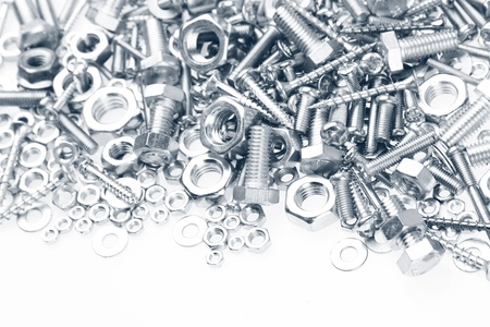 fasteners: Chrome nuts and bolts closeup on plain background Stock Photo
