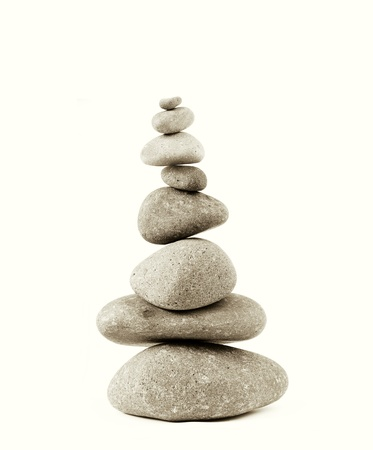 steadiness: Stack of river rocks on plain background