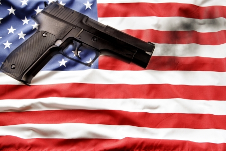 Handgun and American flag. Gun control concept. photo