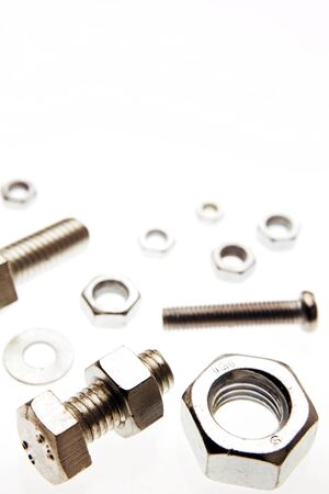 fasteners: Closeup of nuts and bolts on plain background