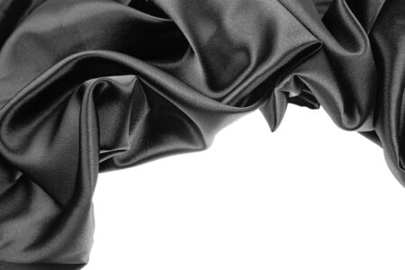 Closeup of rippled black silk fabric on plain background photo