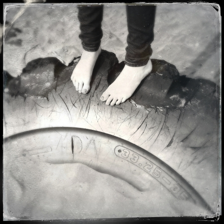 human toe: Feet standing on tyre in sand