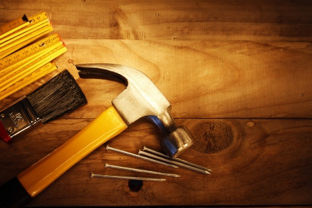 Hammer, nails, ruler and brush on wood photo