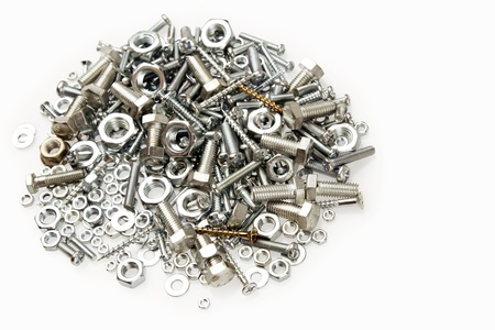 fasteners: Pile of nuts and bolts on plain background