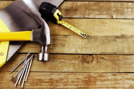 Hamer, spijkers, meetlint en zag op hout Stockfoto