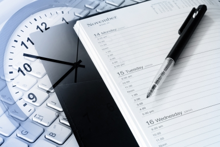 business event: Pen, diary, clock and computer keyboard