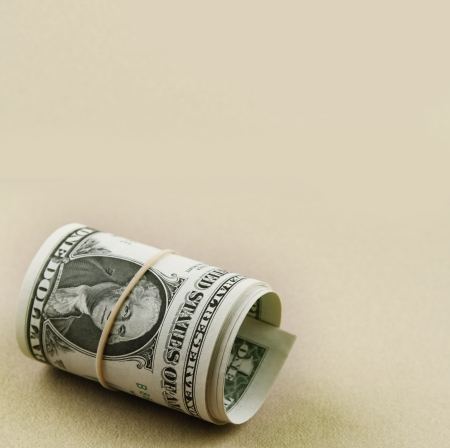 Roll of dollar banknotes on plain background. Copy space photo