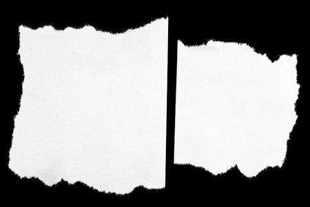 Pieces of torn paper on black. Copy space photo