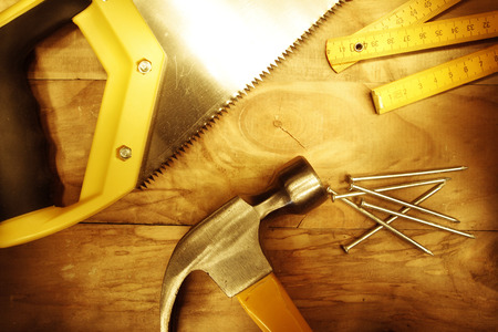 woodworking: Hammer, nails, ruler and saw on wood
