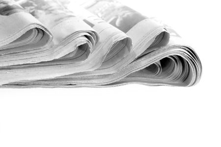 Closeup of newspapers on plain background photo