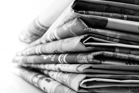 newspaper stack: Closeup of newspapers on plain background