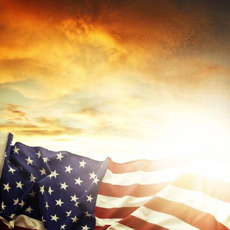 american states: American flag in front of bright sky