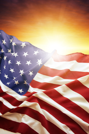 american flag: American flag in front of bright sky