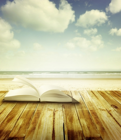 Open book on deck in front of beach scene photo