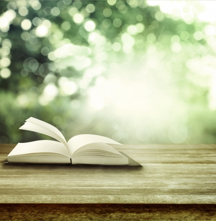 Open book on table in front of spring background photo