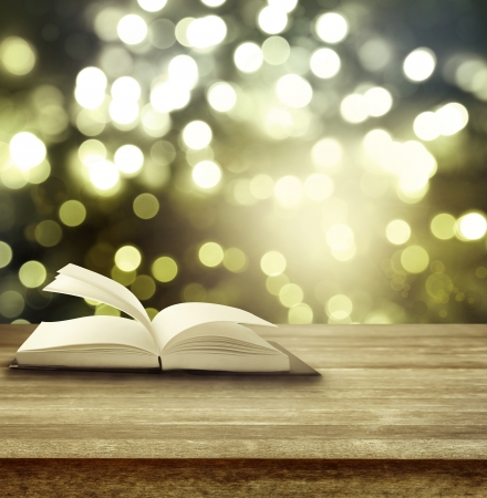 magics: Open book on table in front of blurred lights Stock Photo