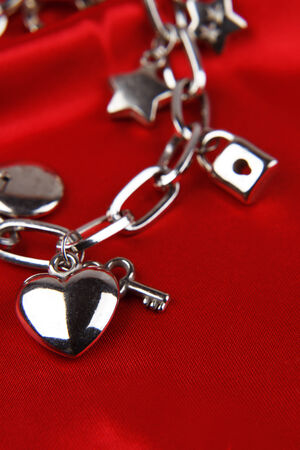 loveheart: Closeup of heart and key on charm bracelet