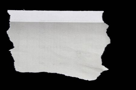 Piece of torn paper on black. Copy space photo