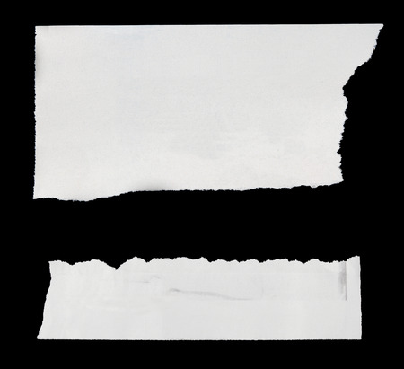 newsprint: Pieces of torn paper on black. Copy space