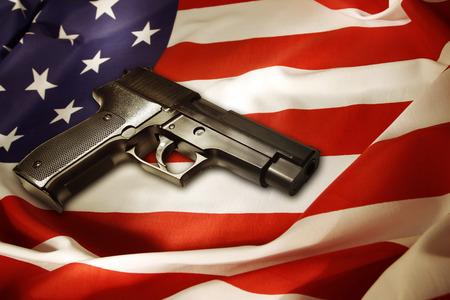 アメリカの国旗の上に横たわるハンドガン 写真素材