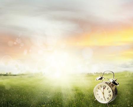daylight savings time: Alarm clock in sunlit spring field