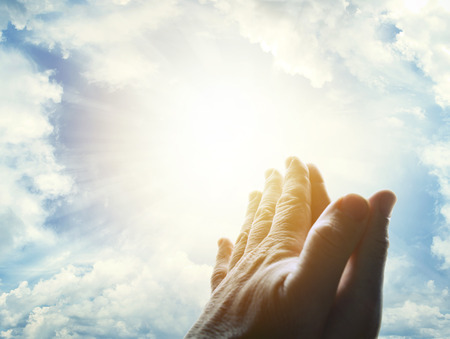 to believe: Hands together praying in bright sky Stock Photo