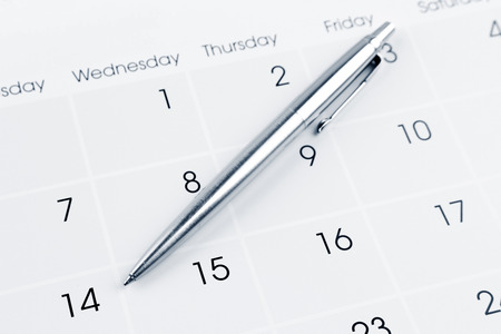 Pen on calendar page closeup photo