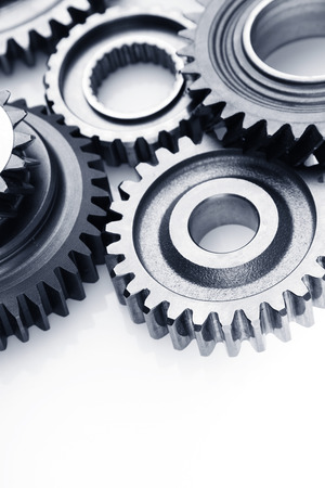Closeup of metal cog gears on plain background. Copy space photo