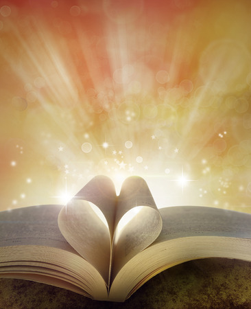 bible christmas: Pages of book in shape of love heart in front of magical background