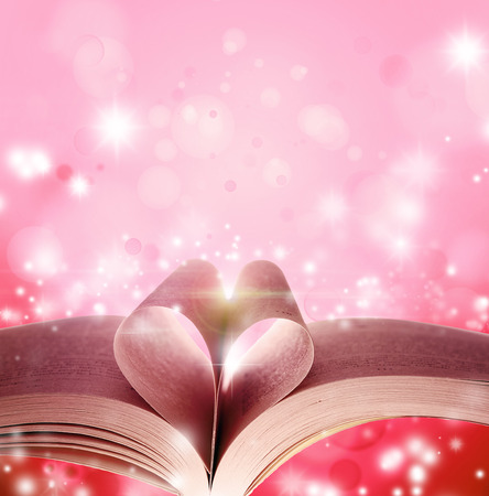 Pages of book in shape of love heart in front of magical background photo