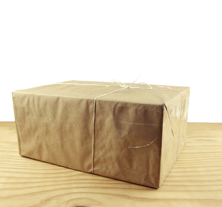 Wrapped package on table top in front of white photo