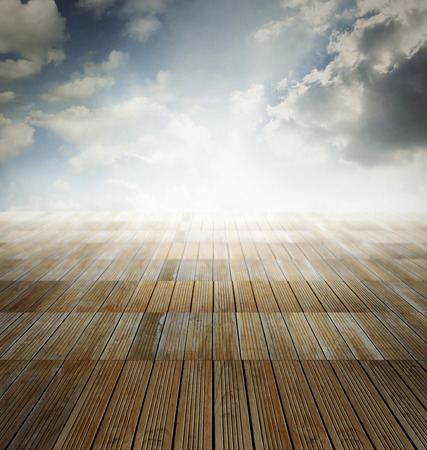 Wooden floor leading to bright sky photo