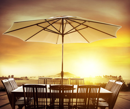Table, chairs and umbrella outdoors in front of sunny scene photo