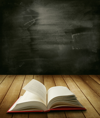 Open book on table in front of blackboard photo