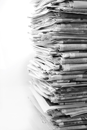 Pile of newspapers on plain background photo