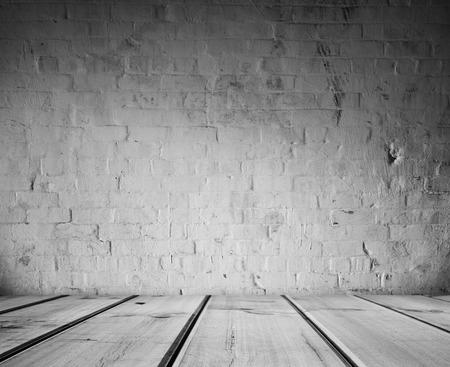 floorboards: Wooden floorboards and brick wall