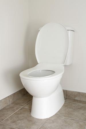White toilet in bathroom, lid open  Stock Photo