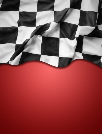 Checkered black and white flag on red background. Copy space photo