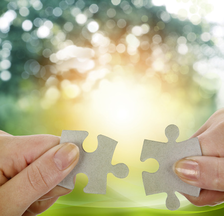 solve problems: Fingers holding two puzzle pieces