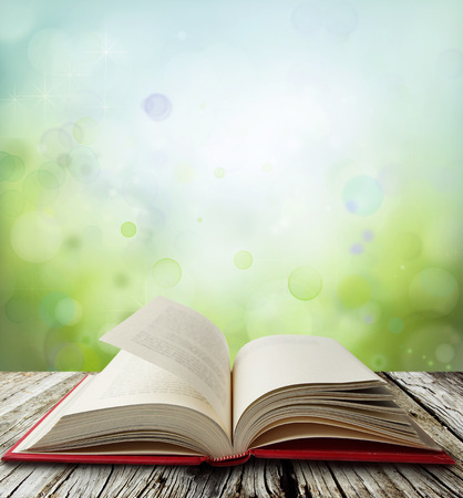 Open book on table in front of green blue  background photo