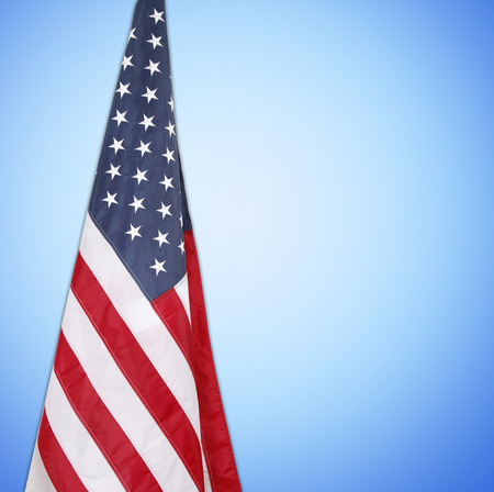 American flag in front of blue background Stock Photo